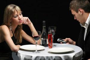 Una pareja cena en un restaurante y ella está aburrida mientras él mira su móvil